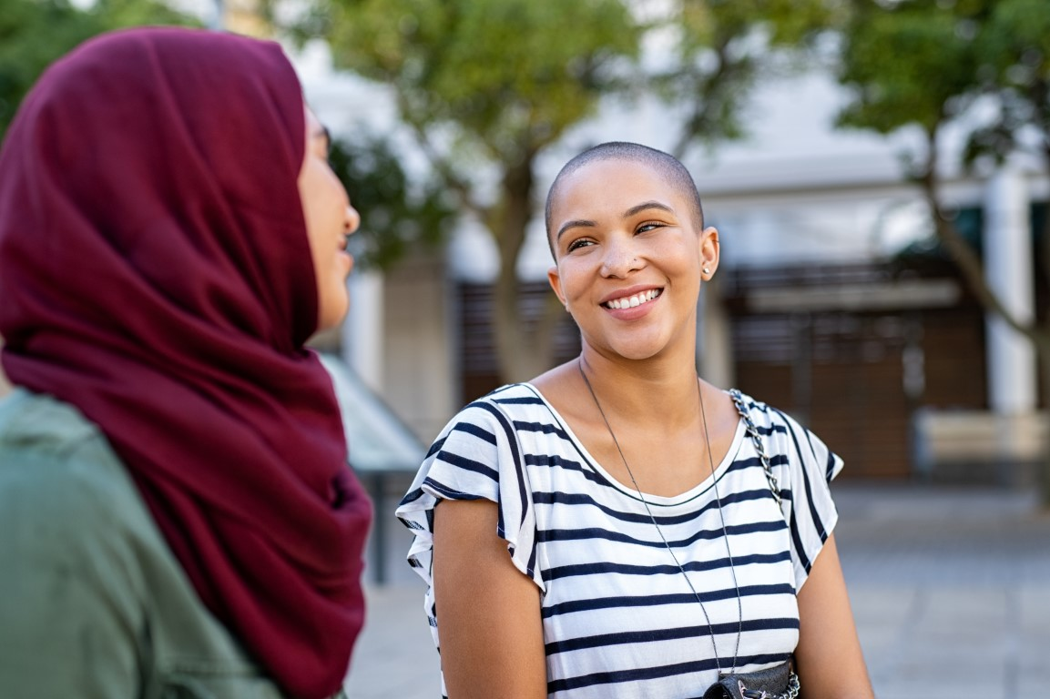 Cheerful woman in conversation with friend in hijab.
