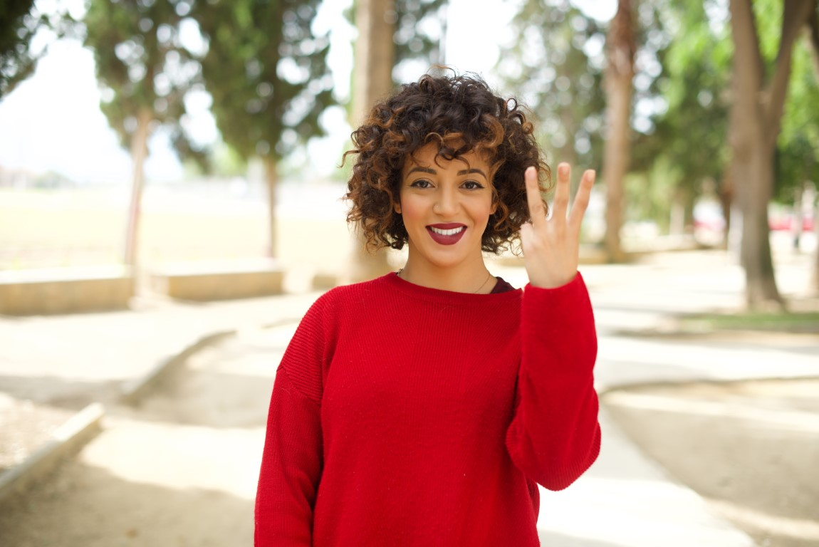 Woman wearing red shirt holding up three fingers