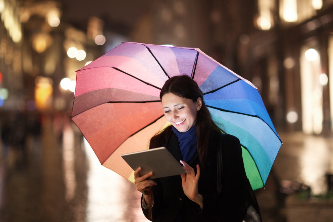 Woman with colorful umbrella using tablet computer outdoor. She standing in the city street in the rainy evening