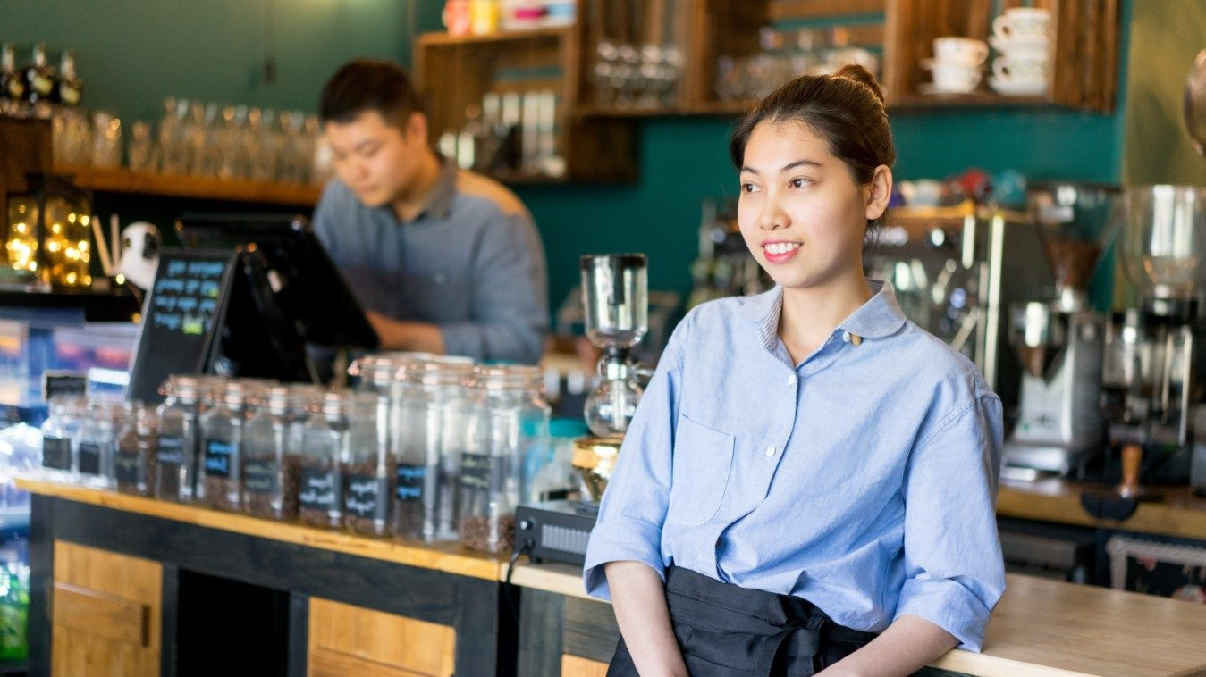 Asian waitress leaning on bar counter and enjoying her work.